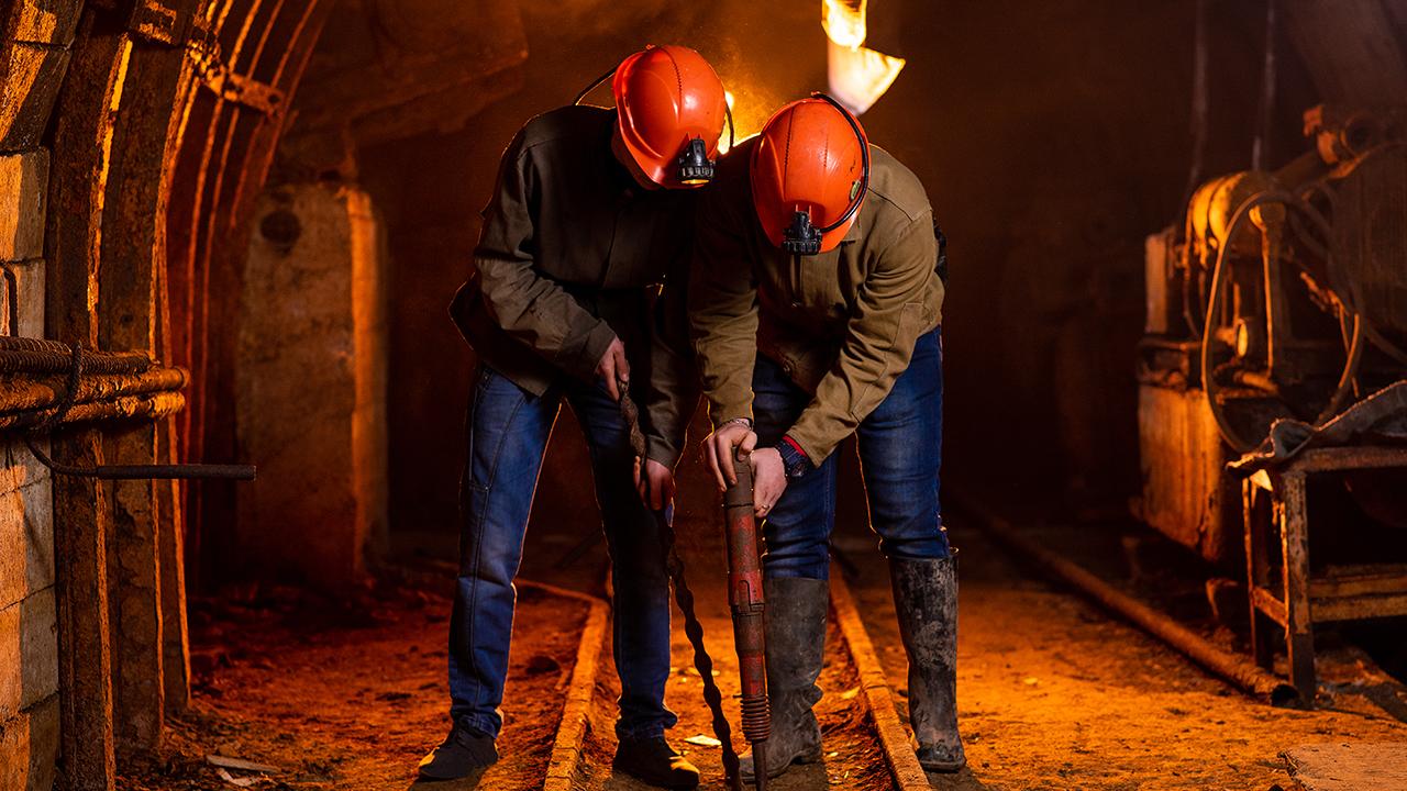 Dwóch młodych chłopaków w roboczych mundurach i kaskach ochronnych wykonuje prace w kopalni