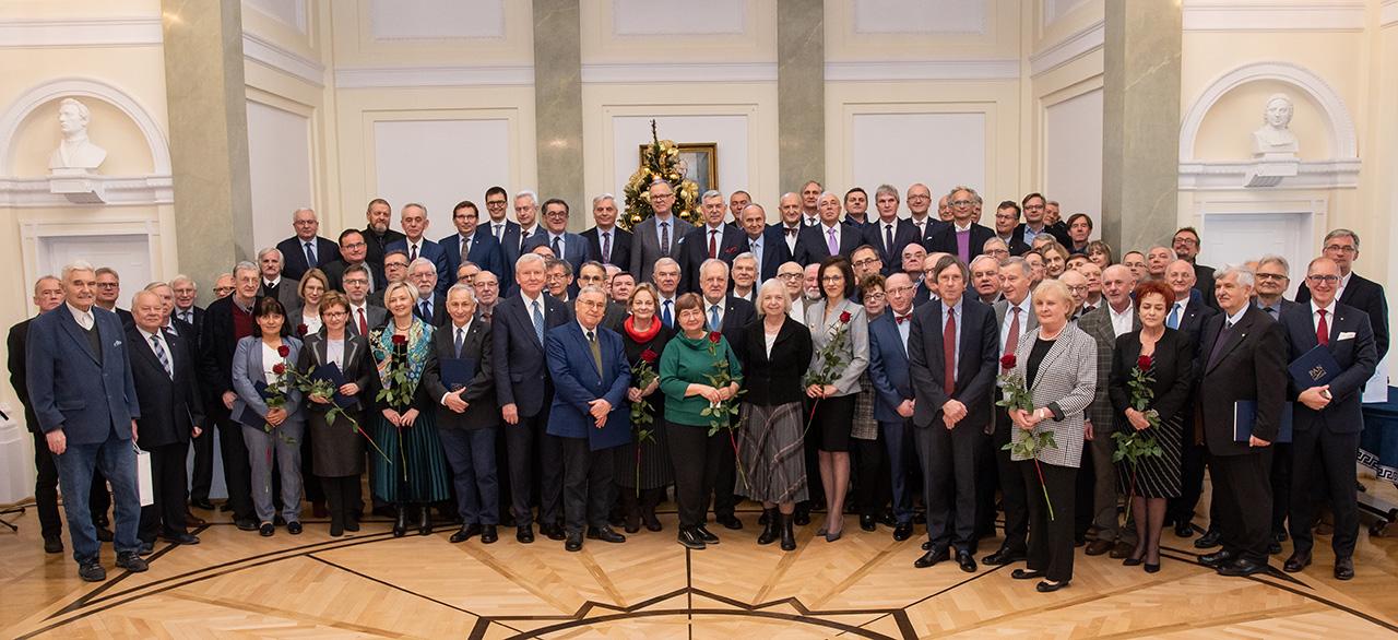 Pamiątkowe wspólne zdjęcie nowych członków PAN, w tle choinka