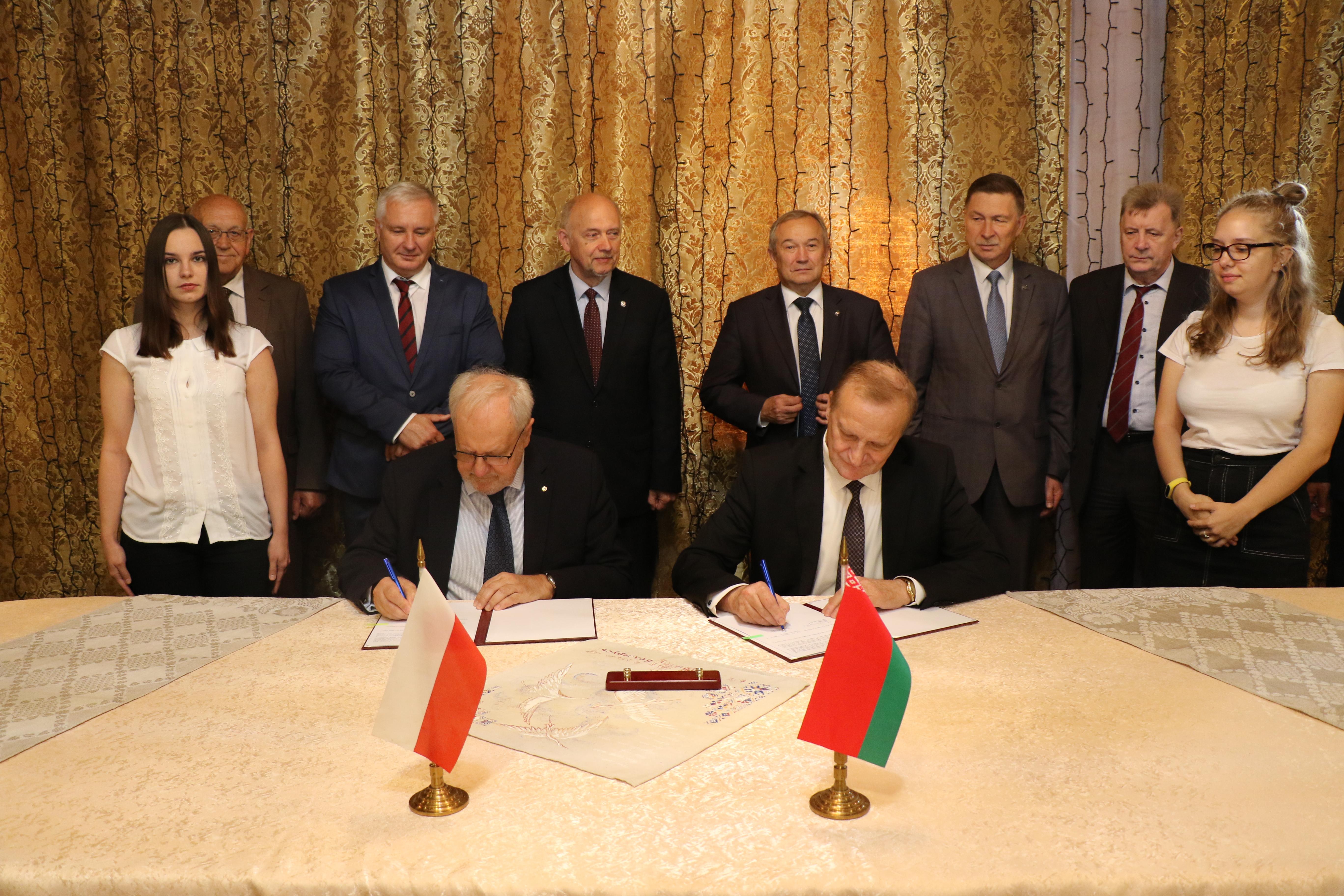 Prezesi PAN i NASB podpisują umowę w otoczeniu współpracowników