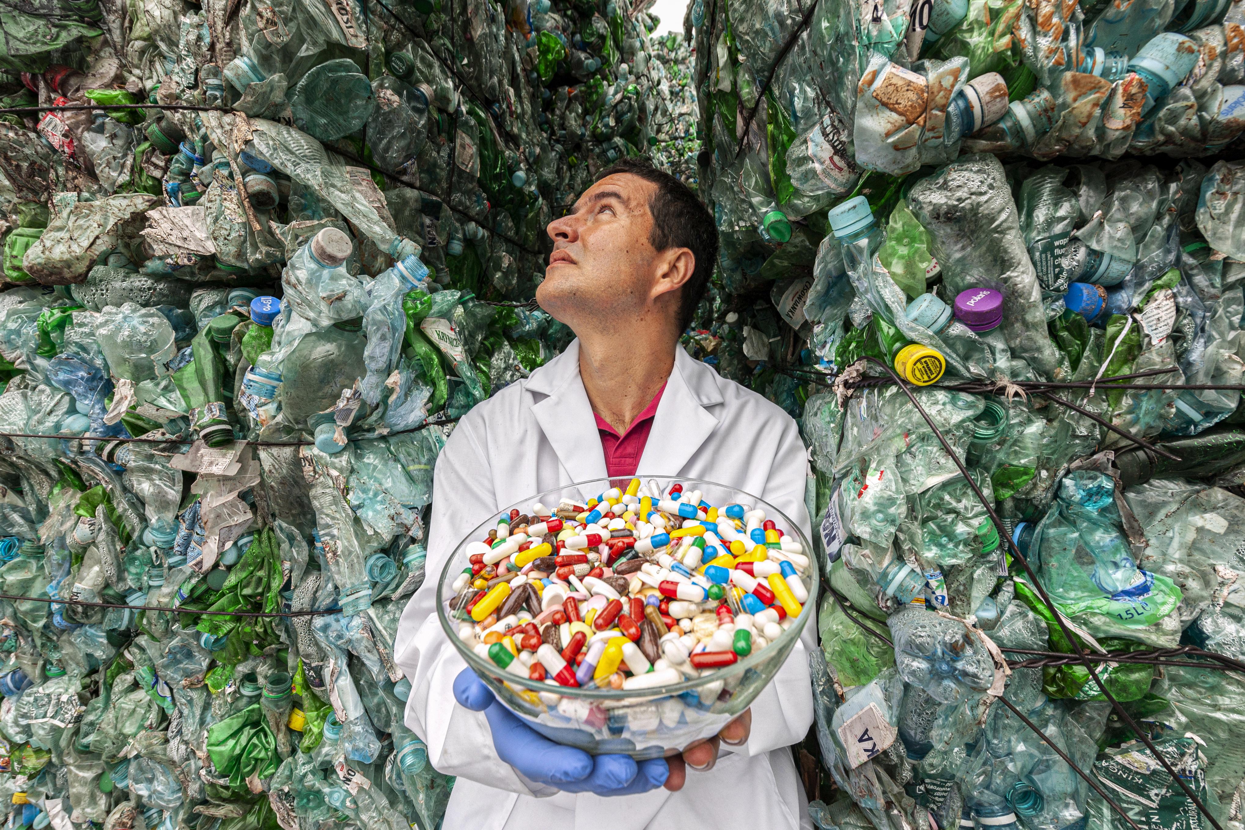 Naukowiec trzyma misę z lekami, w tle góry z plastikowych butelek