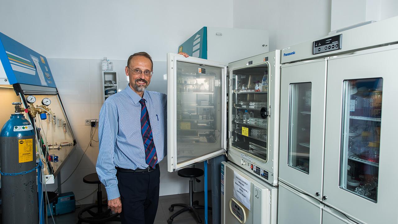 Prof. Leszek Kaczmarek w laboratorium, otwiera lodówkę z probówkami