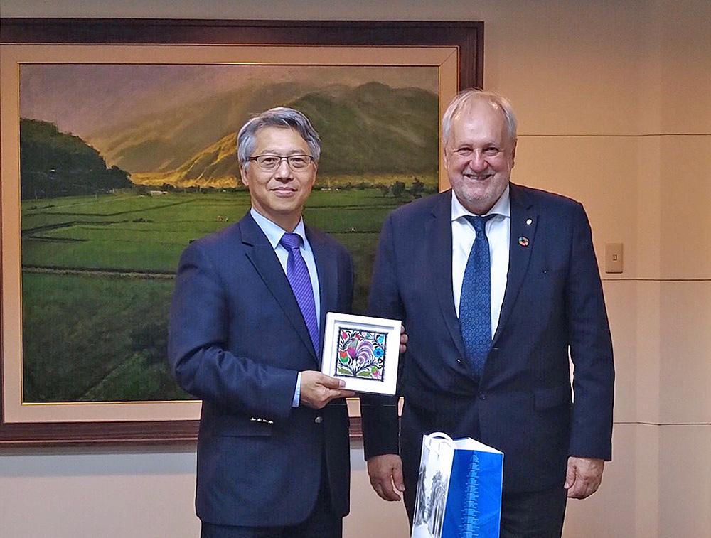 Prezes tajwańskiej akademii nauk pokazuje łowicką wycinankę koguta. Obok uśmiechnięty prezes PAN