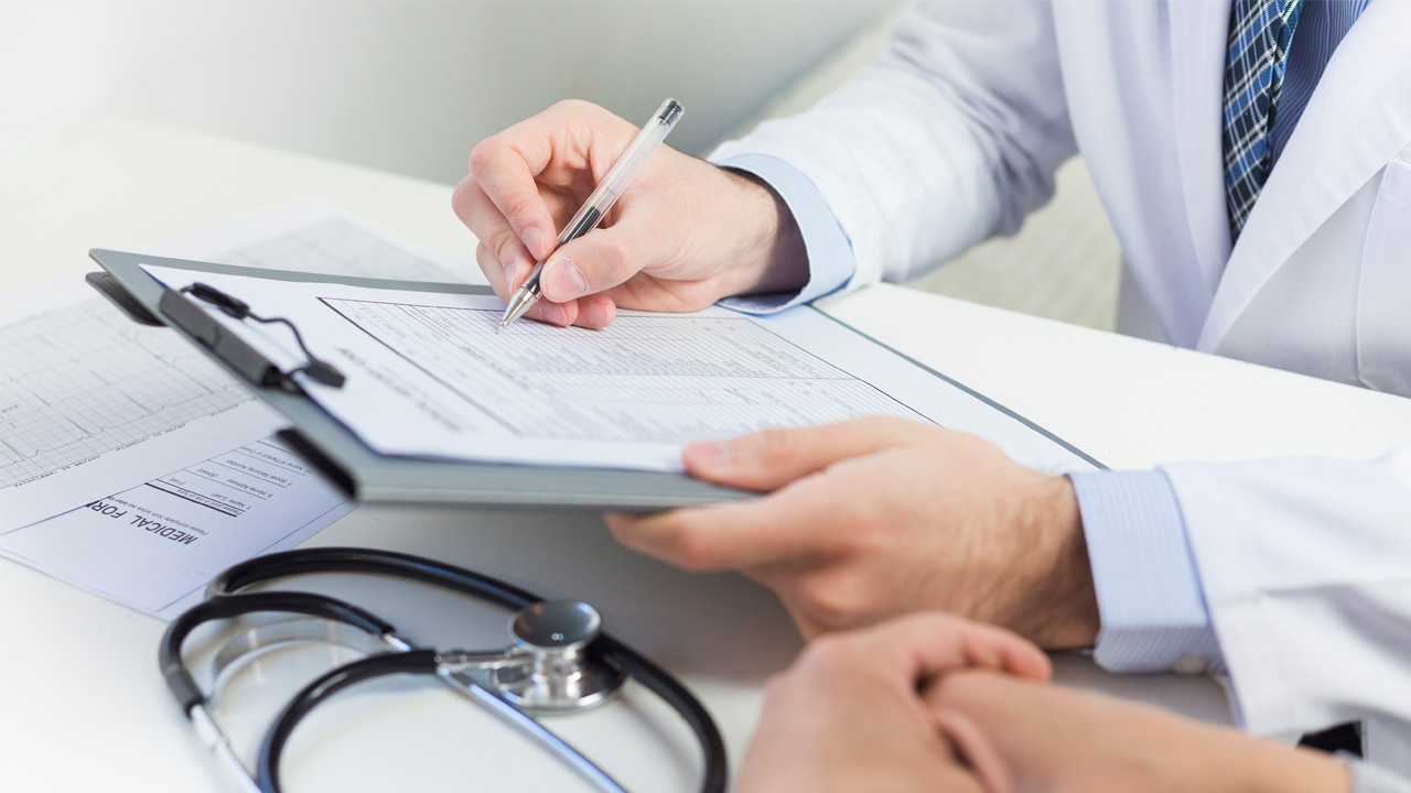 Lekarz wypełniający kartę pacjenta